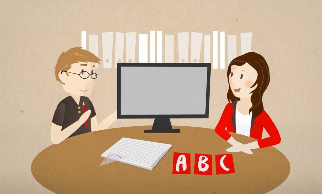 Frau und Mann sitzen im Gespräch an einem Tisch mit Schreibblock und Monitor
